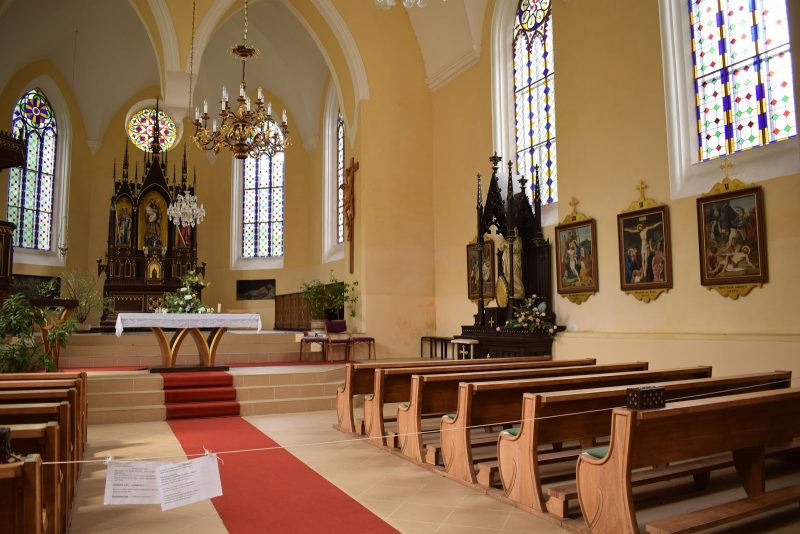 Interior of a church with wooden pews and an orange carpeted aisle.