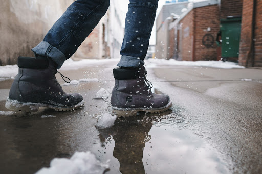 Close-up of lower legs and feet in boots, standing in a puddle with slush on the surrounding ground.