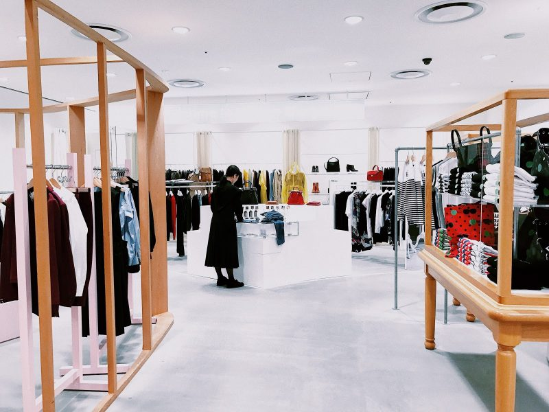 Woman standing in the middle of a clothing store.