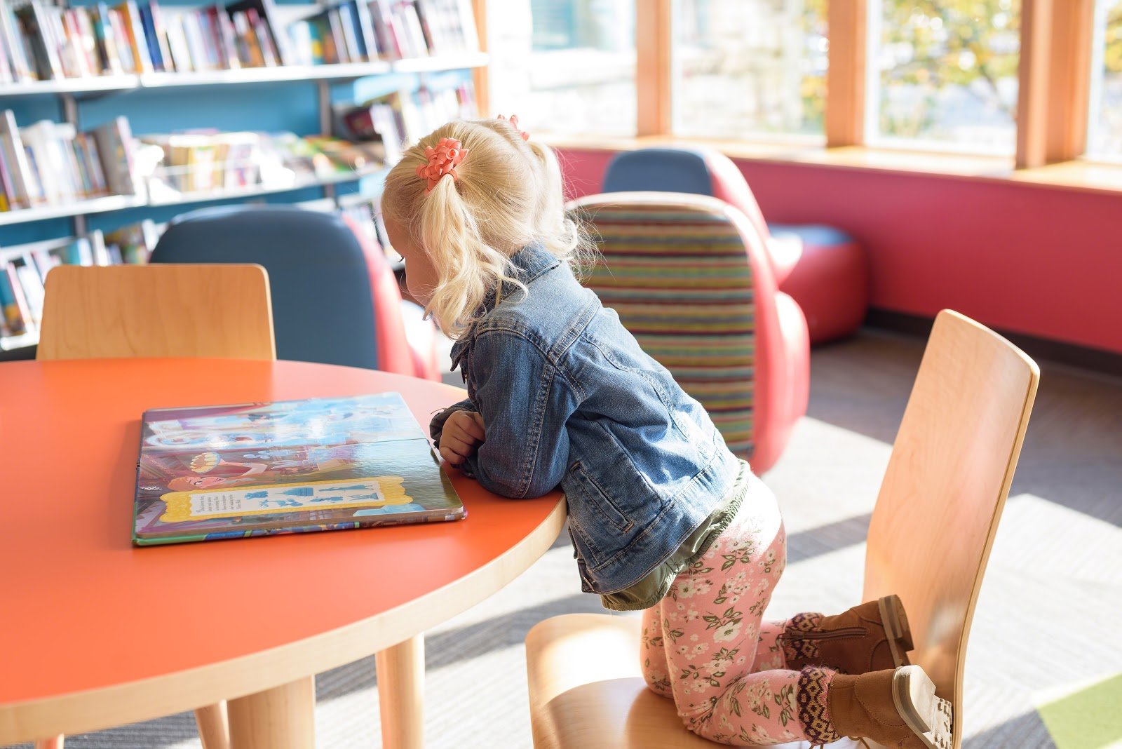 Little girl kneeling on a chair and reading a picture book at a round table.