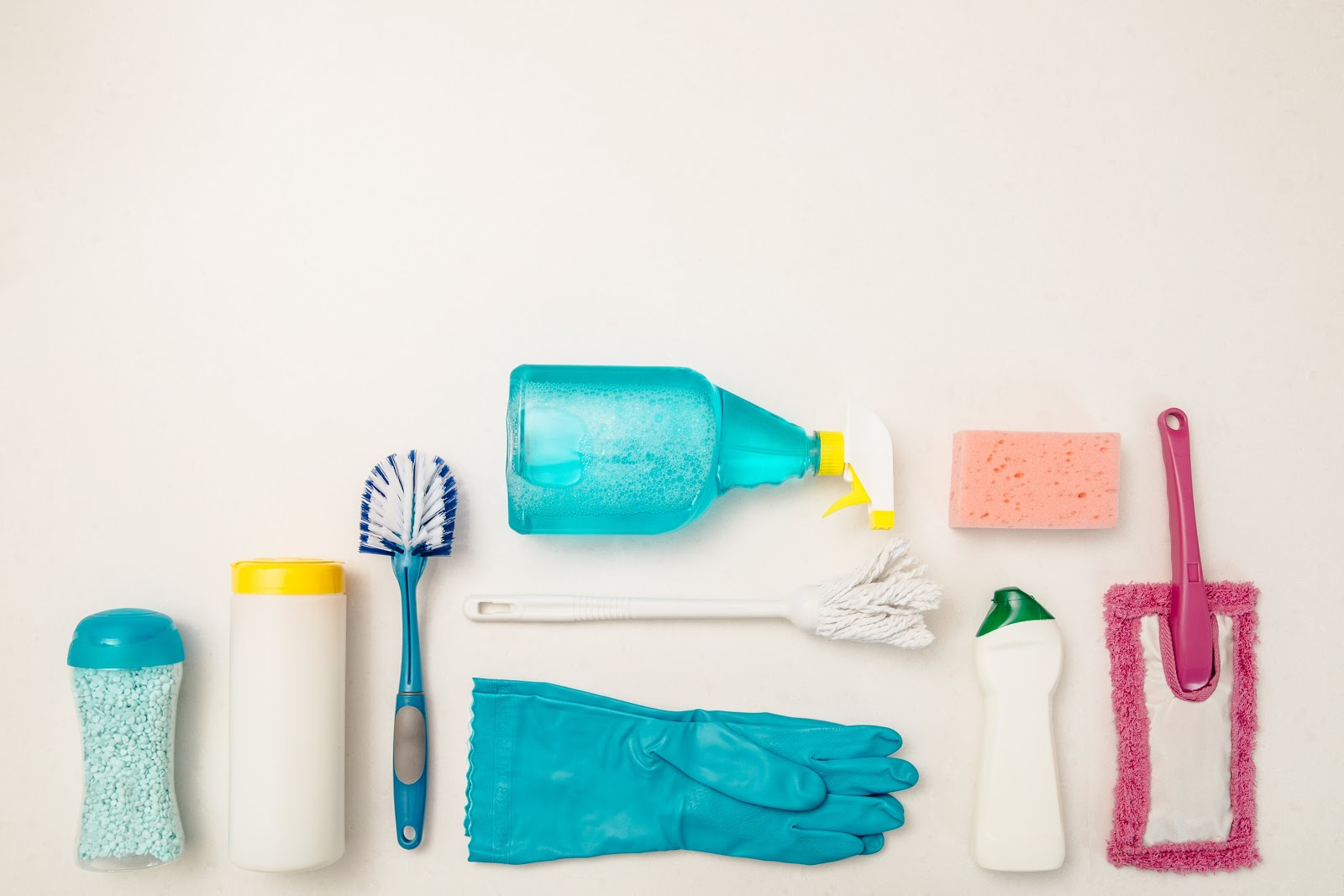 Various cleaning products laid out on a white background.