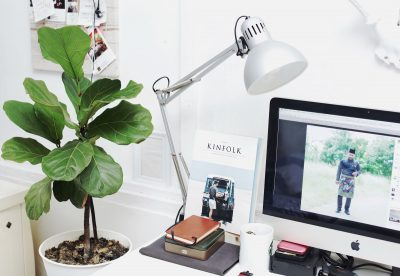 White desk with computer, notebooks, lamp, and houseplant.