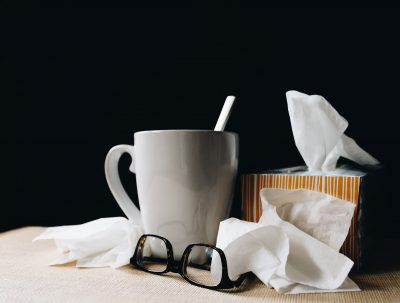 White mug, eyeglasses, box of tissues, and used tissues clustered together on a white surface with a black background.