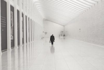 Man in a black suit walking through an all-white room with glossy tile floors.