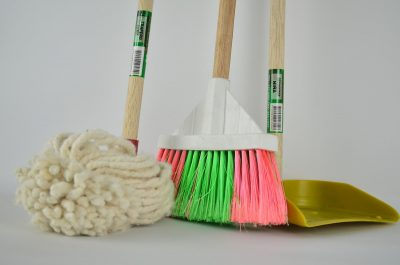 Close-up of a mop, broom, and dustpan.