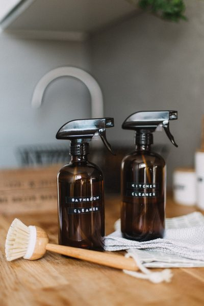 """a wooden-handled scrub brush and two brown spray bottles with the labels """"bathroom cleaner"""" and """"kitchen cleaner."""""""