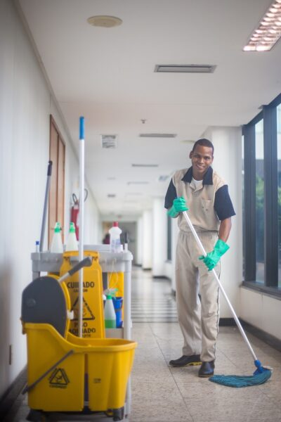 A man wearing rubber gloves mopping the floor of a commercial space.