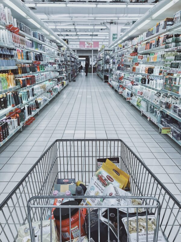 Shopping cart full of groceries in an aisle of a large retail store.