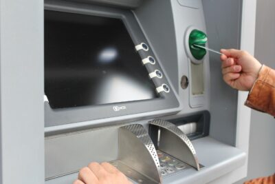 Bank machine with a hand inserting a card into the machine.