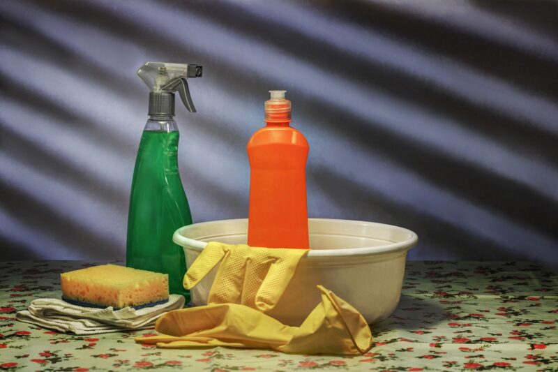 two bottles of cleaner, a sponge, rubber gloves, and a white basin.