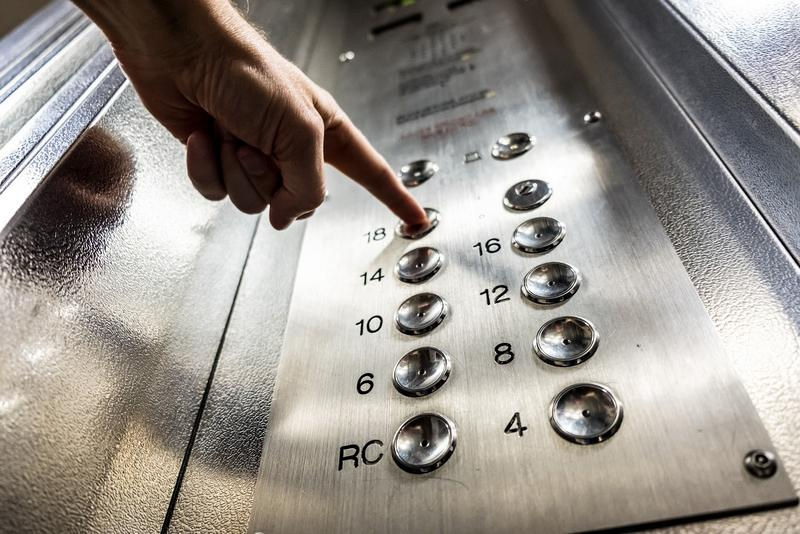 Elevator buttons with a hand pushing one of them.
