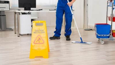 "Janitor seen from the waist down mopping an office floor next to a yellow ""Caution Wet Floor"" sign."