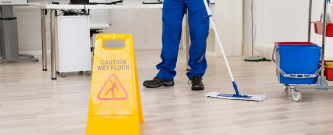 """Janitor seen from the waist down mopping an office floor next to a yellow """"Caution Wet Floor"""" sign."""