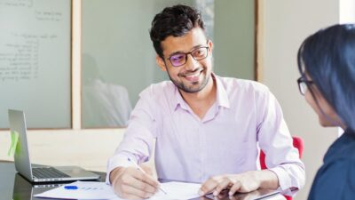 Young man at a desk smiling while signing a contract.