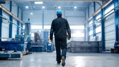 Worker in a blue hard hat walking across a factory floor.
