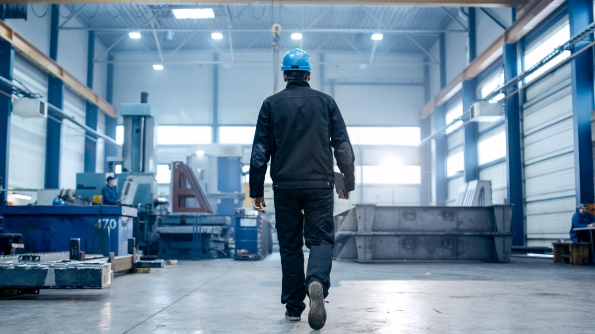 Worker in a blue hard hat walking across a factory floor.