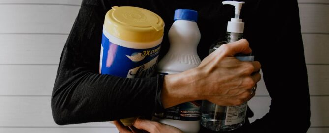 Woman seen from the neck down holding cleaning products in her arms.