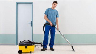 Man dressed in blue vacuuming a carpeted floor.