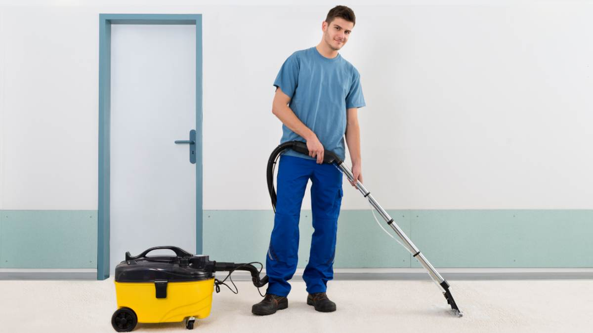 Man dressed in blue vacuuming a carpeted floor.