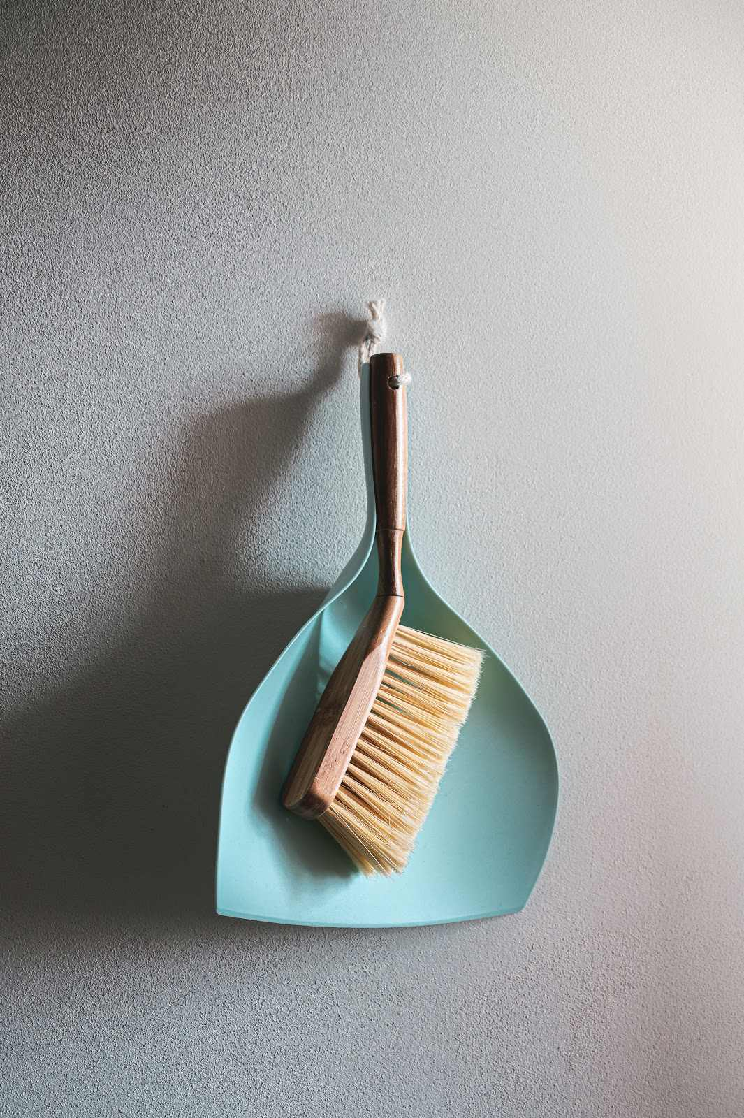 Small wooden hand broom and light blue dustpan hanging on a white wall.