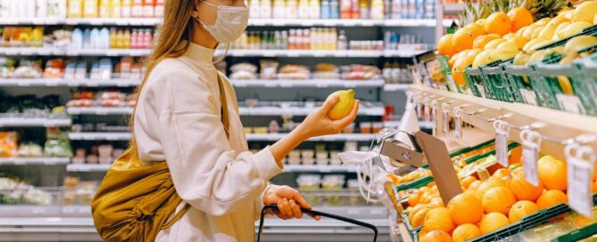 woman wearing a mask in a supermarket, holding a grocery basket and a lemon.