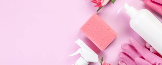 white cleaner bottles next to pink rubber gloves, fresh flowers, and a sponge on a pink background.