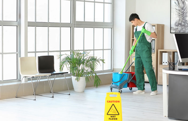 A janitor in a green jumpsuit mopping the floor of an office.