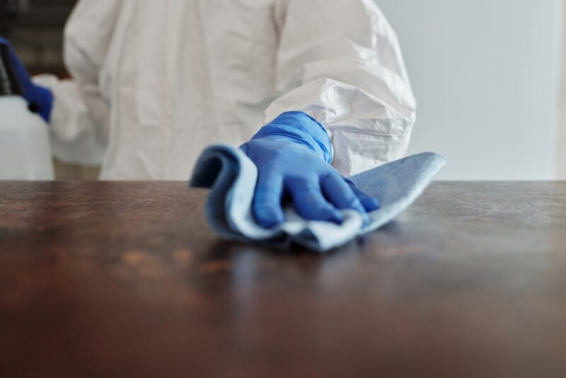 A cleaner in gloves wiping down a wooden surface with a microfiber cloth.