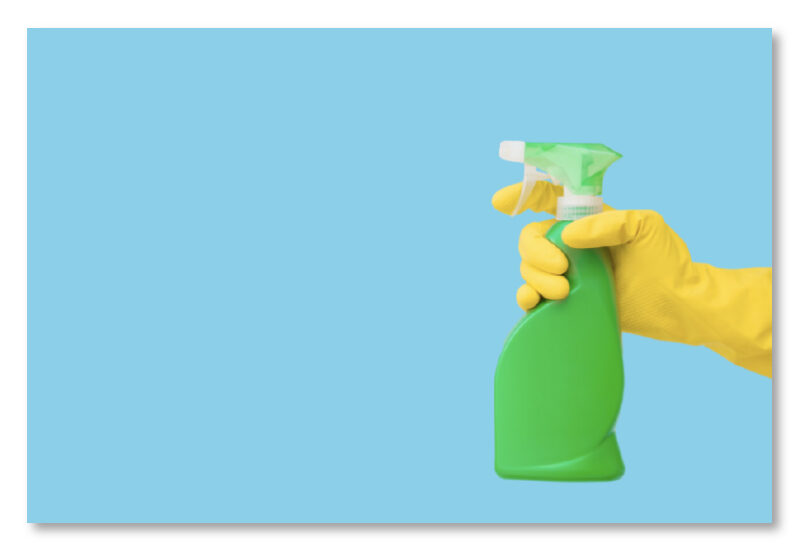 green spray bottle of cleaning product being held by a hand with a yellow glove on