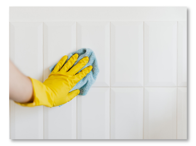 washing tiles with a yellow glove on