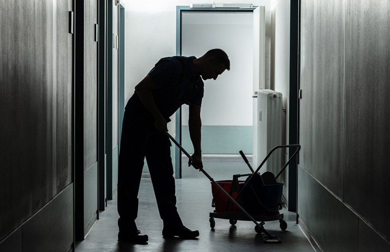 Janitor cleaning an apartment building corridor.