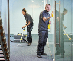 two cleaners cleaning carpet and glass windows
