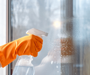 window cleaning with an orange glove on