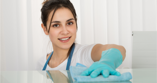 A cleaner wearing rubber gloves and wiping down a white surface with a cloth.