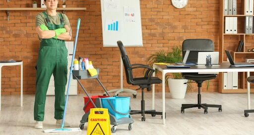 Professional cleaner in an office with a mop and cleaning cart.