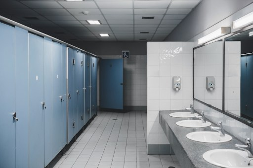 A bathroom with multiple stalls and sinks.